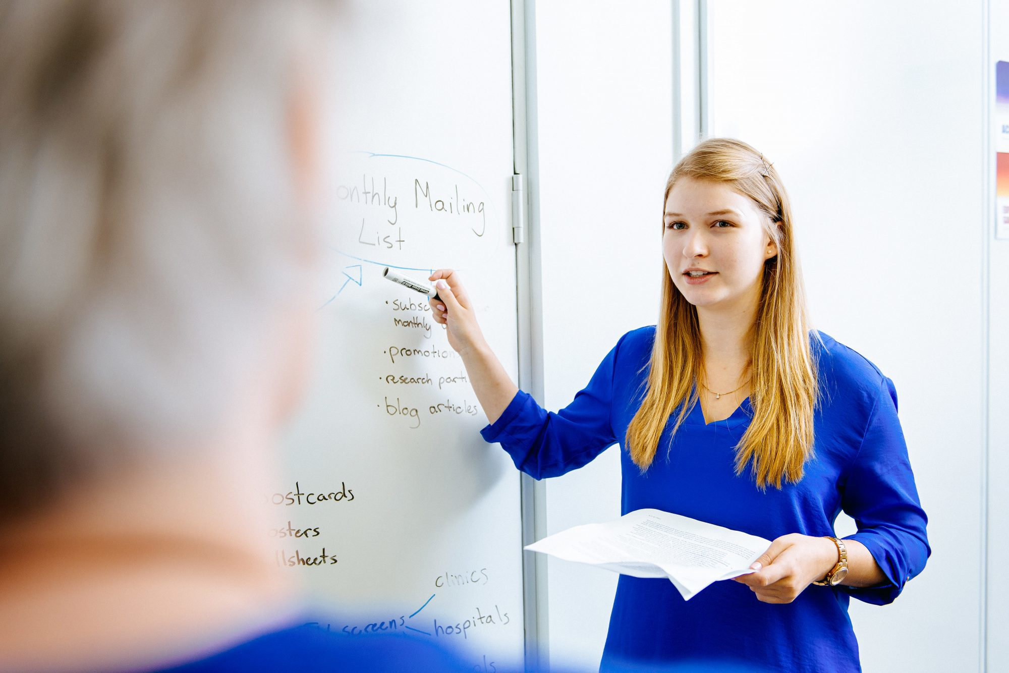 A girl presenting something from a whiteboard